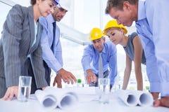 Lag av affärsfolk som ser konstruktionsplan Royaltyfri Bild