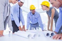 Lag av affärsfolk som talar om konstruktionsplan Arkivfoto