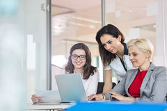Lag av affärskvinnor som i regeringsställning använder bärbara datorn på tabellen arkivbild