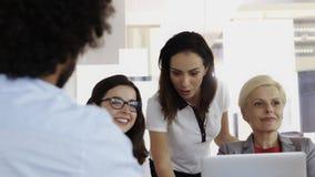 Lag av anställda som tillsammans arbetar på datoren i deras kontor lager videofilmer