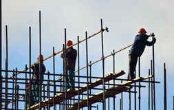 Lag av arbetare som bygger högen med blå himmel på bakgrunderna fotografering för bildbyråer