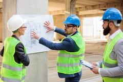 Lag av arkitekter och affärspartners som ser arkitektoniska teckningar och ritningar arkivfoton