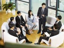 Lag av asiatiskt affärsfolk som i regeringsställning möter arkivfoto