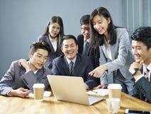Lag av asiatiskt affärsfolk som tillsammans i regeringsställning arbetar royaltyfria bilder