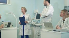Lag av blandade medicinska personaler som skrattar i kontoret arkivfilmer