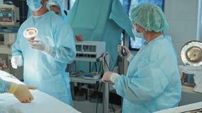 Lag av doktorer i sterila kläder och maskering under kirurgi l?ngsam r?relse lager videofilmer