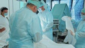 Lag av doktorer i sterila kläder och maskering under kirurgi l?ngsam r?relse arkivfilmer