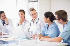 Lag av doktorer och sjuksköterskor som diskuterar Arkivbild