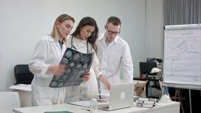 Lag av doktorer som arbetar på bärbara datorn och analyserar röntgenstrålen i medicinskt kontor arkivfilmer