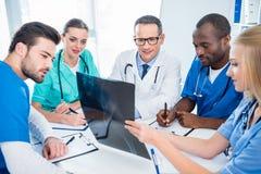 Lag av doktorer som diskuterar röntgenstrålebildläsning arkivfoto