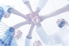 Lag av doktorer som tillsammans sätter händer på ljus bakgrund medicinsk service royaltyfria foton