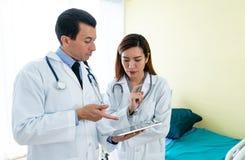 Lag av doktorn som undersöker till medicinska rapporter arkivfoto