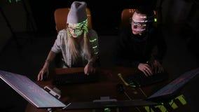 Lag av en hacker och att hacka datorer som arbetar i mörkt rum stock video