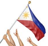 Lag av folkhänder som lyfter den Filippinerna nationsflaggan Fotografering för Bildbyråer