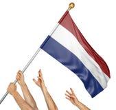 Lag av folkhänder som lyfter den Nederländerna nationsflaggan Royaltyfri Fotografi