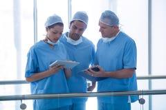 Lag av kirurger som diskuterar över den digitala minnestavlan Royaltyfri Bild
