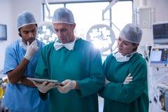 Lag av kirurger som diskuterar över den digitala minnestavlan i operationrum Royaltyfri Bild