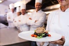 Lag av kockar med en som framlägger en maträtt arkivfoton