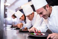 Lag av kockar som avslutar efterrättplattor i köket royaltyfria foton