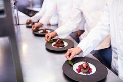 Lag av kockar som avslutar efterrättplattor i köket royaltyfria bilder