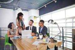 Lag av lyckat affärsfolk som har ett möte i utövande solbelyst kontor Arkivbild