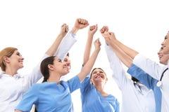 Lag av medicinska doktorer som tillsammans lyfter händer på vit bakgrund arkivbilder