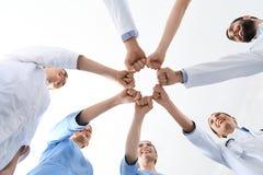 Lag av medicinska doktorer som tillsammans s?tter h?nder p? vit royaltyfri foto