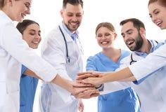 Lag av medicinska doktorer som tillsammans sätter händer på vit bakgrund royaltyfria bilder