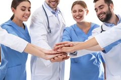 Lag av medicinska doktorer som tillsammans s?tter h?nder p? vit silhouettes det bl?a begreppsfolket f?r bakgrund skyenhet arkivbild