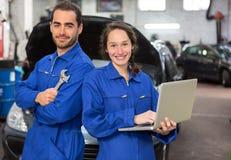 Lag av mekaniker som arbetar på garaget royaltyfria bilder