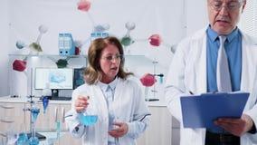 Lag av mogna forskare som talar, medan gå i modernt laboratorium arkivfilmer