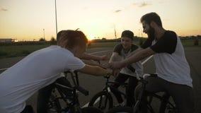 Lag av pojkar med cyklar som uttrycker framgång för lagbyggnad som trycker på deras händer och stiger de - stock video