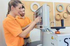 Lag av snickare som programmerar CNC-maskinen i deras seminarium Arkivfoton