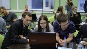 Lag av studenter som tar en aktiv del i konkurrens av unga professionell Två män och en kvinna arbetar tillsammans stock video