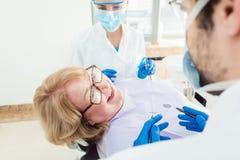 Lag av tandläkare som talar till den höga patienten i deras kirurgi Royaltyfri Bild