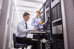Lag av tekniker som använder den digitala kabelanalysatorn på serveror Fotografering för Bildbyråer