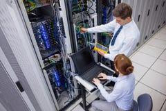 Lag av tekniker som använder den digitala kabelanalysatorn på serveror Royaltyfri Bild