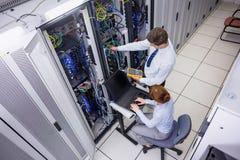 Lag av tekniker som använder den digitala kabelanalysatorn på serveror Royaltyfri Foto