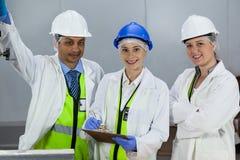 Lag av tekniker som står i köttfabrik royaltyfri bild