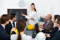 Lag av teknikerer och arkitekter som diskuterar affärsprojekt och Arkivfoton