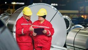 Lag av teknikerer som har diskussion på den industriella stålväxten arkivfilmer