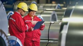 Lag av teknikerer som har diskussion på den industriella stålväxten stock video