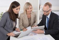 Lag av tre affärspersoner som tillsammans sitter på skrivbordet i ett möte Arkivbilder