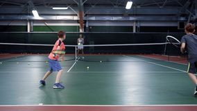 Lag av två pojkar som spelar tennis mot en äldre flicka eller tennislagledare arkivfilmer
