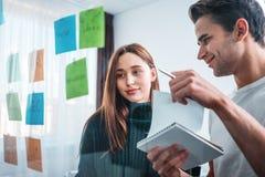 Lag av unga coworkers som möter, och för affärsidéer för idékläckning den nya stolpen för bruk som han noterar för att dela idé royaltyfri bild