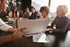 Lag av ungdomarsom går över skrivbordsarbete Fotografering för Bildbyråer
