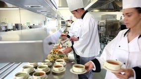 Lag av upptagna kockar som arbetar på beställningsstationen arkivfilmer