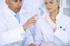 Lag av vetenskapliga forskare i laboratorium som studerar vikter eller blodprövkopian Ny vaccin för farmakologiindustr Royaltyfri Bild