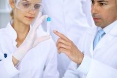 Lag av vetenskapliga forskare i laboratorium som studerar vikter eller blodprövkopian Ny vaccin för farmakologiindustr Arkivbild