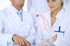 Lag av vetenskapliga forskare i laboratorium som studerar vikter eller blodprövkopian Ny vaccin för farmakologiindustr Fotografering för Bildbyråer